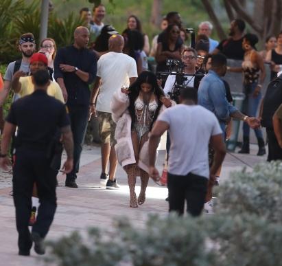 Nicki Minaj wears a fur coat over a white bikini while filming new video in Miami Beach.